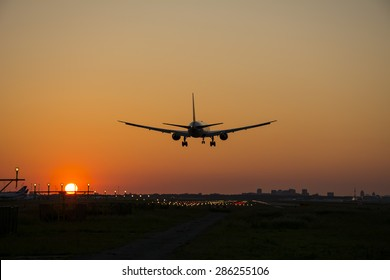 Passenger plane is landing during a beautiful sunrise.