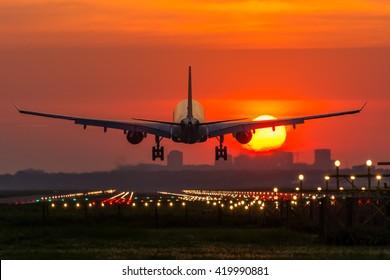 Passenger plane is landing during a wonderful sunrise.