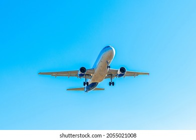 The passenger plane  is landing on the runway, landing at the international airport. Air transportation, air travel. Clear cloudless sky. Vacation flights.