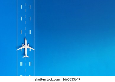 The passenger plane on airport runway and blue background with empty space for text. Top view, copy space