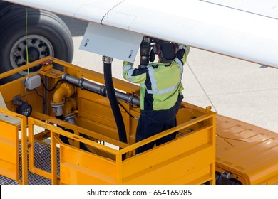 Passenger plane preflight service before departure. Ground staff prepare aircraft for the flight. Technician refueled airplane through the filling valve in the wing.