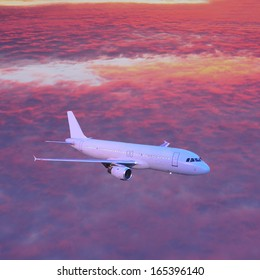 Passenger plane in the sky above the clouds at sunset.