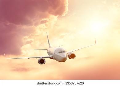 Passenger plane in the sky at sunrise or sunset, vacation and travel