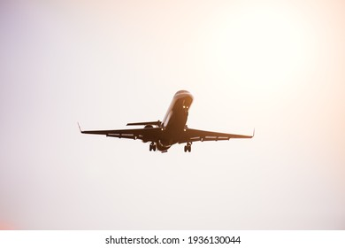 Passenger plane in the sky at sunrise or sunset. Vacation and travel concept