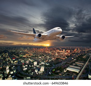 A passenger plane in the sunset cloudy sky. Aircraft flies high over the city quarters. Urban landscape above view.