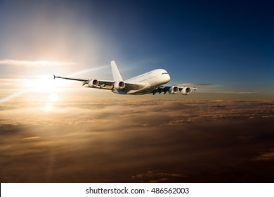 A passenger plane in the sunset sky. Aircraft flying above the clouds on a background of the bright sun.