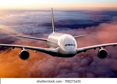 Passenger plane in the sunset sky. Aircraft flying above the clouds. Airplane front view.