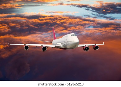A passenger plane in the sunset sky. Front view. Aircraft flying high above the orange clouds.