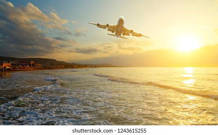 Passenger plane is taking off on the background of the sea shore at dawn and sunset