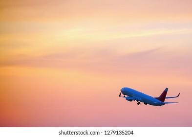 Passenger plane taking off over the evening orange sky.
