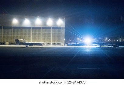 Passenger planes near hangar at night airport.