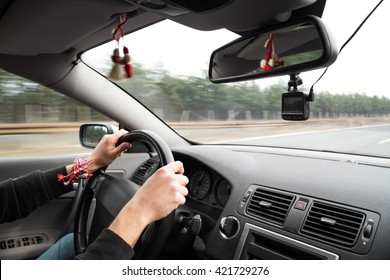 Passenger point of view on driver with hands on steering wheel moving down highway with trees in background outside window. Traditional Bulgarian martenitsa hanging on the roof.