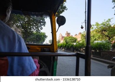 (Passenger point of view) A unidentified driver is riding his auto rickshaw (also known as Tuc Tuc) through the busy streets of the pink city of Jaipur. Beautiful Hawa Mahal in the background.