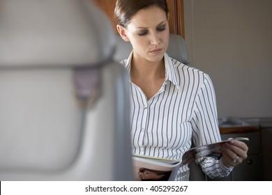 A passenger reading a magazine on a flight