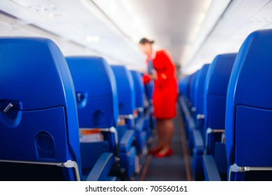 Passenger seat in airplane, Interior of airplane and stewardess background. Stewardess renders services for passengers. Service concept, travel concept.