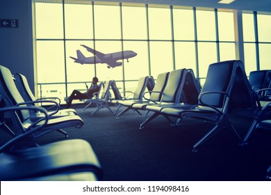 Passenger seat in Departure lounge for see Airplane, view from airport terminal, waiting for  Boarding,sun light in vintage color selective focus, transport and travel concept