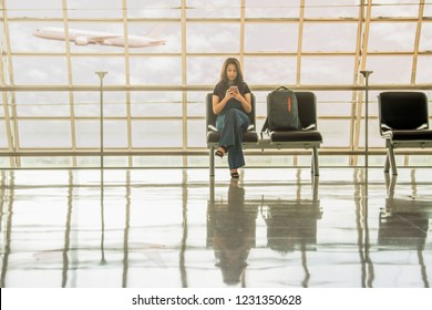 Passenger seat in departure for see airplane, Asian woman playing smartphone, checking e-mail on mobilephone while sitting on bench in airport gate windows at planes on airport runway. Copy space