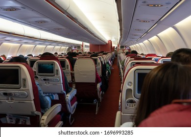 Passenger seat, Interior of airplane with passengers sitting on seats and stewardess walking the aisle in background