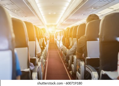 passenger seat, Interior of airplane with passengers sitting on seats and stewardess walking the aisle in background. Travel concept,vintage color