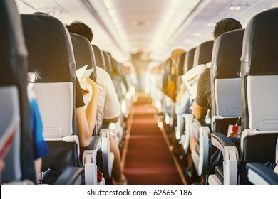 passenger seat, Interior of airplane with passengers sitting on seats and stewardess walking the aisle in background. Travel concept,vintage color,selective focus