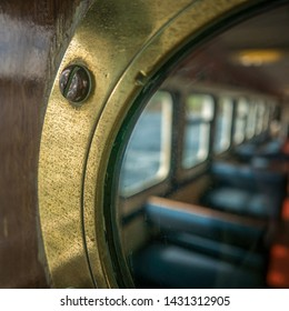 Passenger Seating Through A Brass Porthole On A Ship Or Ferry