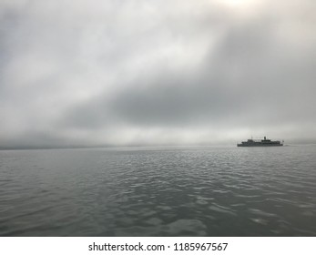 Passenger ship on a dramatic and foggy morning on Ammersee in Bavaria, Germany