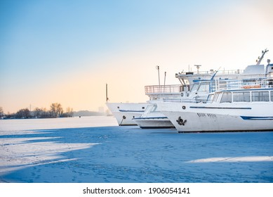 Passenger ships in dock on frozen river. Boats on ice