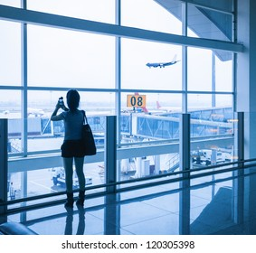 passenger silhouette in airport window and flight arrival