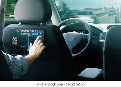 Passenger sitting in the backseat and  selects a route when autonomous taxi rides on the highway.