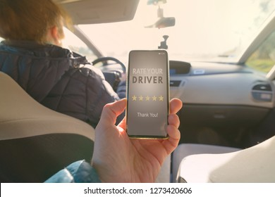 Passenger is sitting on the back seat of the car and using smart phone app to rate a driver. Taxi or modern peer to peer ridesharing concept