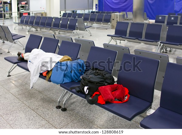Passenger sleeps on seats in an empty night airport after flight cancellation