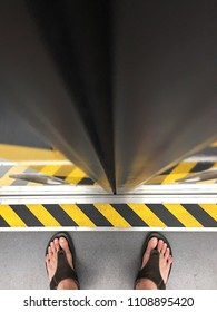 Passenger stands on the train. Caution line beware the gap between train and platform