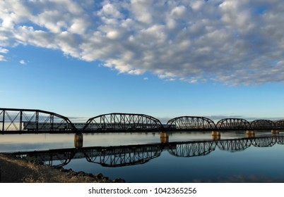 Passenger train crossing a large, calm river at the break of day in the western USA