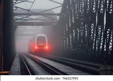 Passenger train on the old iron bridge in mysterious fog - blurred motion