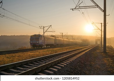 Passenger train on the railway bridge in autumn foggy morning.