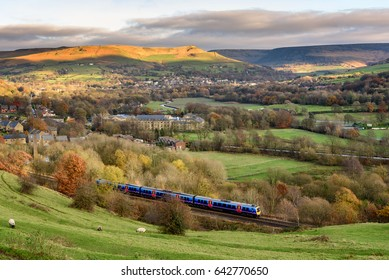 Passenger train passing through british countryside near greater Manchester, England.