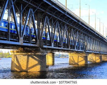 The passenger train travels along a two-level bridge and a railway across the Dnieper  River in the Dnipro city. Dnepropetrovsk, Dnipropetrovsk, Dnepr), Ukraine
