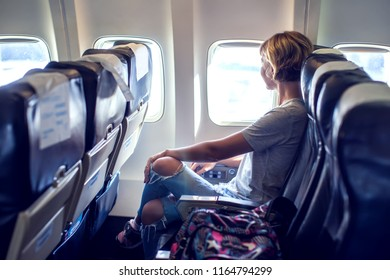 Passenger traveler looking at window in airplane, travel by flight, woman tourist sitting in air plane. Travel concept
