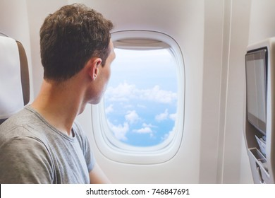 passenger traveler looking at window in airplane, travel by flight, man tourist sitting in air plane