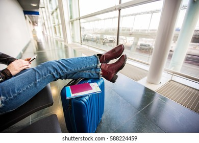 Passenger traveler woman using tablet smart phone in airport waiting for air travel .Young woman sitting with travel suitcase trolley, in waiting hall of departure lounge in airport