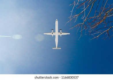 Passenger turboprop plane / regional airplane is flying overhead towards destination airport. front view a few seconds before landing. travel and journey concept.