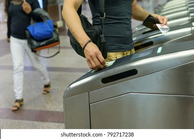 Passenger use ticket passing the entrance at Orchard MRT station