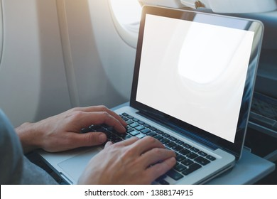 passenger using laptop computer in airplane, onboard wifi internet connection in flight, white empty screen
