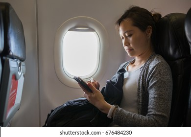 Passenger using smartphone for close to us airplane mode.