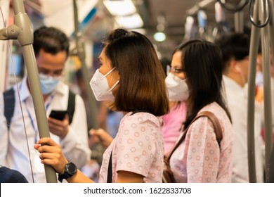 Passenger wearing mouth mask against air smog pollution with PM 2.5 on skytrain in Bangkok city, Thailand 2020.
