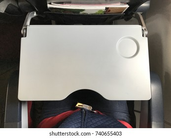 Passenger who wears blue jeans is fastening  red seat belt in airplane cabin. There are tray table and seat belt for passenger in each chair on the plane.