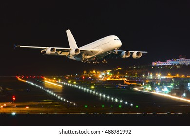 Passenger wide body aircraft. The plane takes off from the airport runway at night.