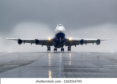 Passenger wide body airliner takes off from wet runway.