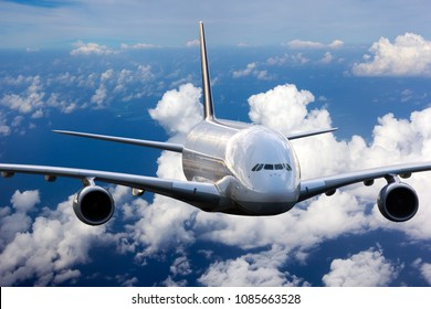 The passenger widebody plane in flight. Aircraft flies high in the blue sky above clouds. Airplane closeup front view.