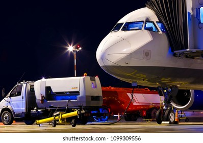 Passenger wide-body plane at the night airport. Airplane nose close up. Side view. Preflight aircraft service before departure. Boarding bridge docked with Airplane.